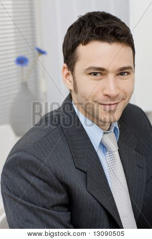 Portrait of happy young businessman at office, smiling.