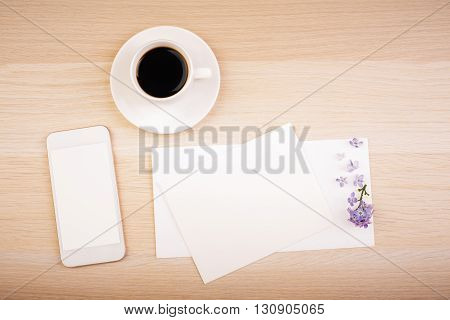Top view of wooden desktop with blank whte smart phone screen empty card and coffee cup. Mock up
