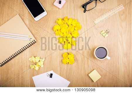 Top view of wooden desktop with crumpled paper lightbulb coffee smartphone and various stationery items. Idea concept. Mock up