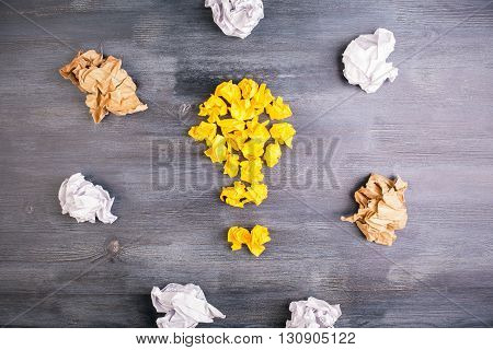 Idea concept with crumpled paper pieces around lightbulb on dark wooden table
