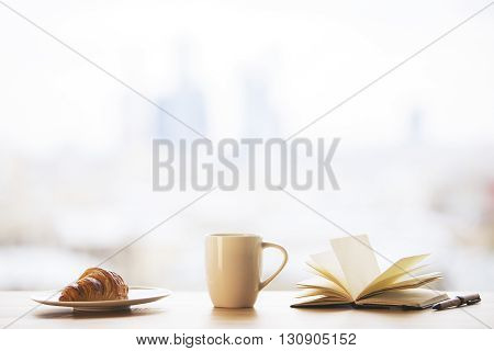 Desktop with tall coffee cup croissant on plate and open book on blurry city background