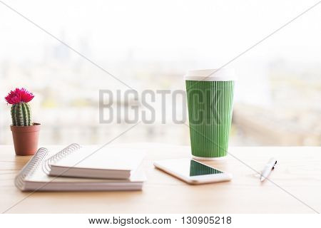 Closeup of wooden desktop with two spiral notepads green coffee cup smart phone cactus and pen on blurry background