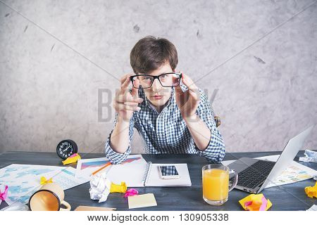 Crazy exhausted man sitting at messy office desk and looking at the camera through eyeglasses