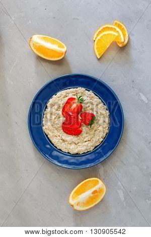 Oatmeal porridge with strawberries and orange slices. Healthy breakfast image