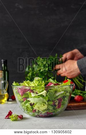 Glass bowl of fresh salad on a dark background. In background mode man holding bunch of parsley