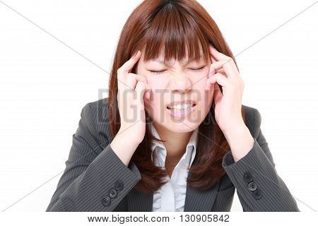 portrait of portrait of young Japanese businesswoman suffers from headache on white background