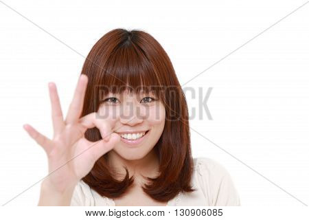 portrait of portrait of Japanese woman showing perfect sign on white background