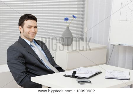 Young businessman sitting relaxed behind office desk with personal organizer, documents and mobil phone.