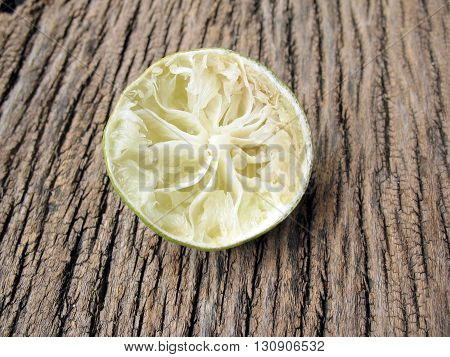 squeezed of lime on wooden texturelemon peel
