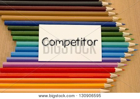 Competitor text concept and colored pencil on wooden background