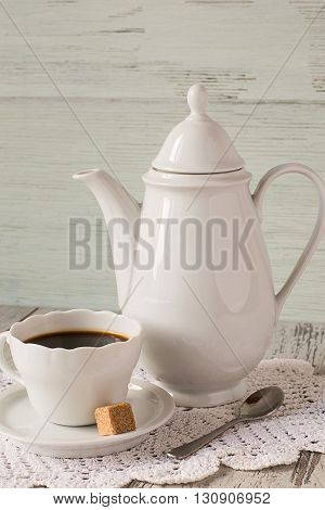 Coffee pot and a cup of coffee on a light wooden background.