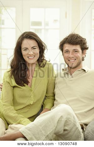 Happy young couple sitting together on couch at home, lokking at camera, smiling.