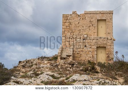 On the top of the hill at Dingli Cliffs island Malta an old house made of stones. Cloudy sky in the background.