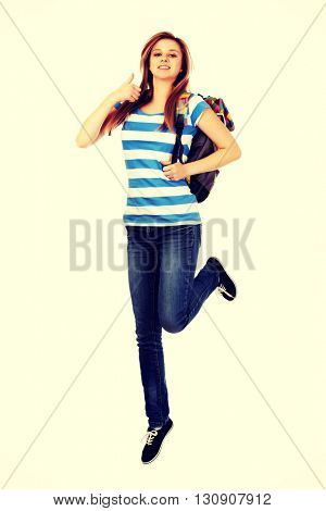 Teenage woman jumping with backpack and thmb up