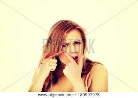 Teenage angry woman poping pimple