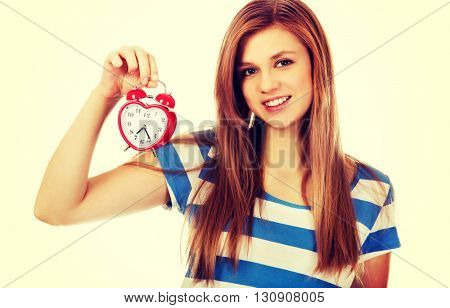 Teenage woman holding alarm clock