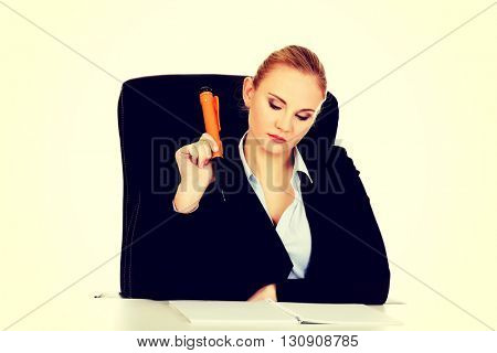 Pensive business woman making notes with a huge pen
