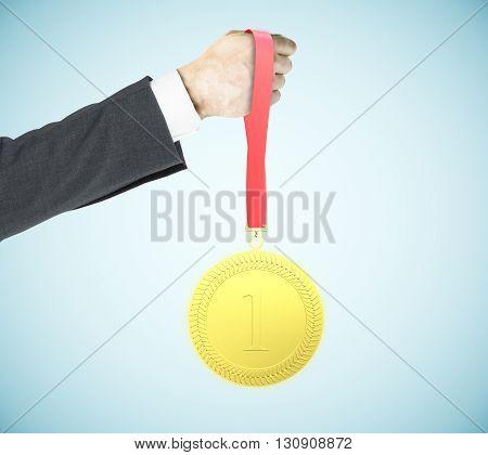 Businessman hand holding first place golden medal on blue background. Leadership concept. 3D Rendering