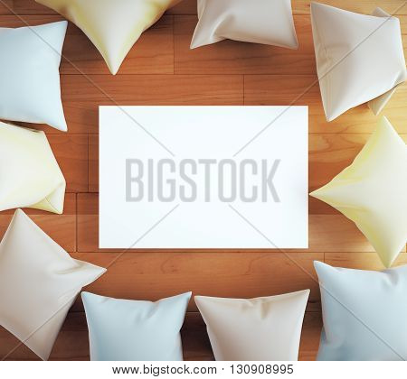 Blank white board surrounded with pillows on wooden floor. Mock up 3D Rendering