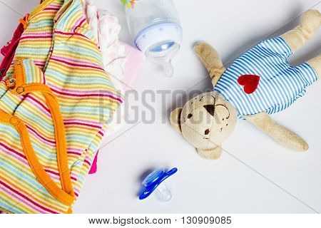 A stack of children's clothing toys pacifier on a white background. Preparing for motherhood. Shopping for baby.