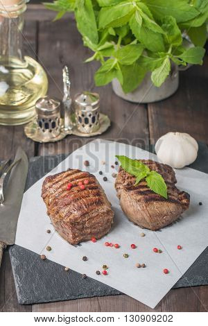 Grilled beef steak close up on paper on wooden table