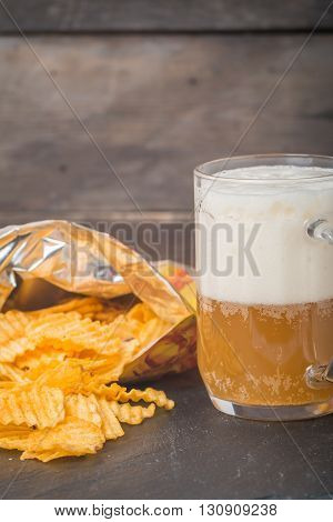 Beer with foam in glass mug and potato chips in bag on wooden table