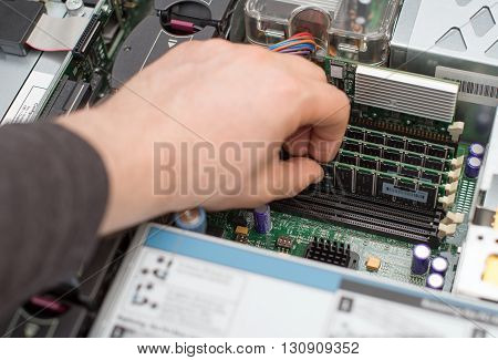 Computer Technician Installing Ram Memory Into Motherboard.