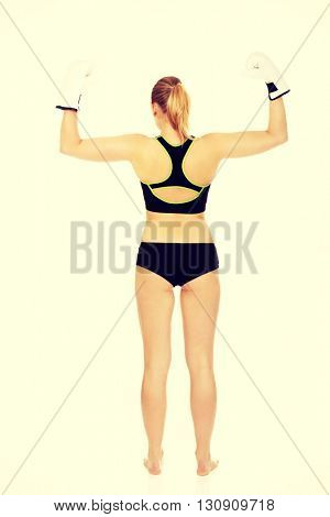 Back view of boxing fitness woman wearing white boxing gloves