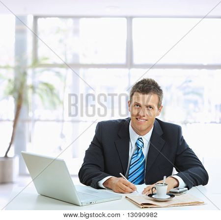 Businessman sitting at table in office lobby, writing note on paper.