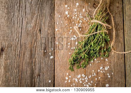 bunch of fresh organic thyme with salt on a wooden background, top view