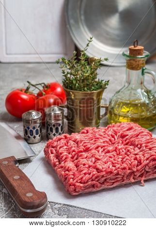 Minced meat on paper with seasoning and fresh thyme on gray background