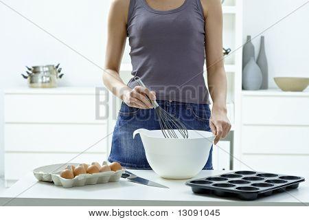 Mujer las manos para batir huevos en un tazón con el batidor de huevo.
