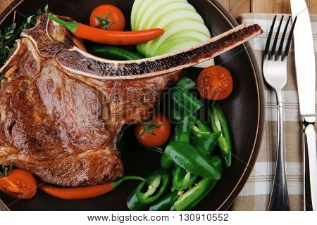 meat food : roast rib on dark dish with thyme pepper and tomato on wooden table