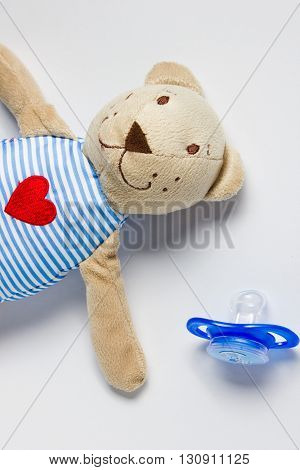 Toy Bear and dummy lying on a white background. Preparing for motherhood. Kids' things.