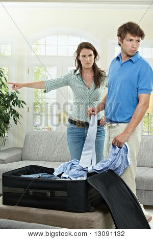 Unhappy couple fighting. Angry woman pointing out, man packing his clothes into suitcase.