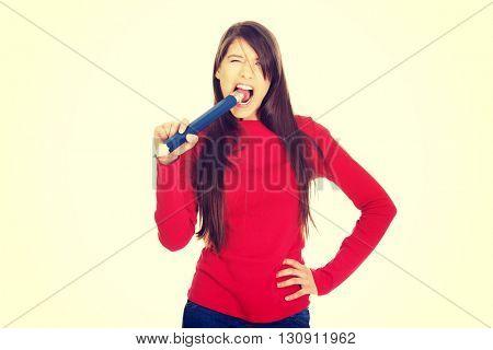 Beautiful young woman biting a pencil.