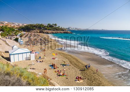 COSTA ADEJE SPAIN - JANUARY 25 2016: People enjoying sunny weather on the picturesque Playa El Duque beach.