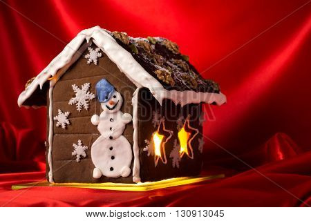 Christmas glazed gingerbread house with sugar snowman and walnuts on housetop. Against red silk background.