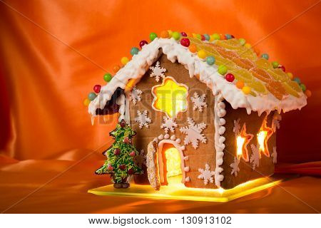Christmas glazed gingerbread house with sweet pine and walnuts on housetop. Against orange silk background.