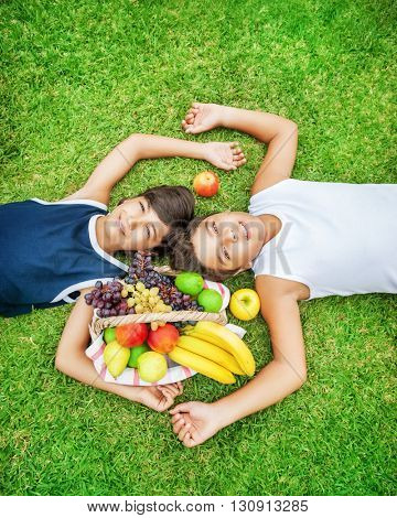 Two happy teen boys lying down on a fresh green grass field, best friends enjoying picnic outdoors, eating many different tasty fruits, healthy nutrition in summer camp
