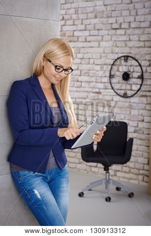 Young blonde woman using tablet computer, standing against wall.