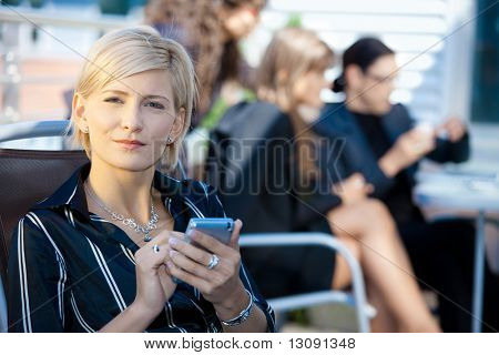 Young businesswoman using smart mobile phone, outside office building.