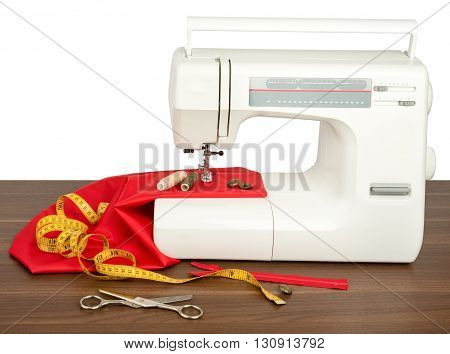 Sewing machine with red fabric, threads and scissors isolated on wood table. Front view