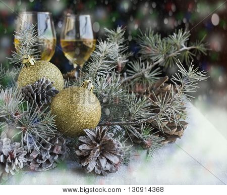 Christmas balls with fir branches, pine cones, and glasses with champagne, card