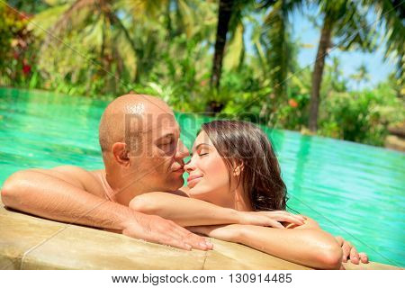 Portrait of a gentle loving couple kissing in a swimming pool, spending honeymoon on a tropical beach resort, happy summer vacation on Bali, Indonesia