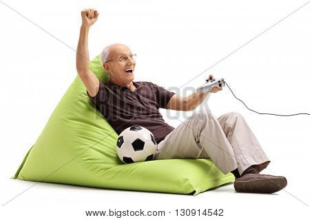 Excited senior man playing a soccer videogame seated on a green beanbag isolated on white background