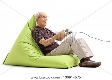 Joyful senior gentleman playing video games seated on a green beanbag isolated on white background