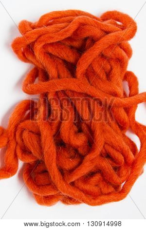 Knitting with wool thick soft orange color yarn. Yarn isolated on white background.