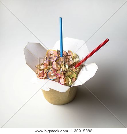 Asian food box filled with colour pencils and pencil shavings.