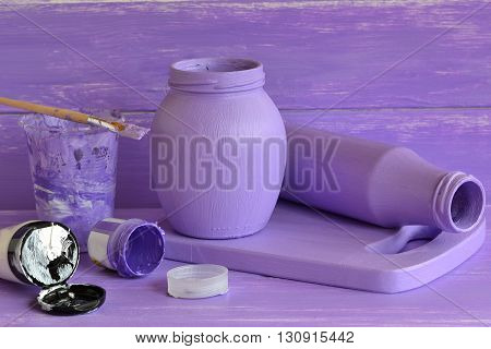 Painted glass jars, tubes of acrylic paint, brush. Interior decorating handmade ideas. Home decorating. Handmade decoration pieces. Making decorative items from waste material.